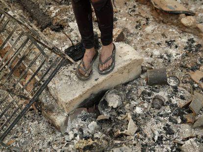 Una joven, sobre las ruinas calcinadas de la casa del novio de su madre tras los incendios en Redding (California).