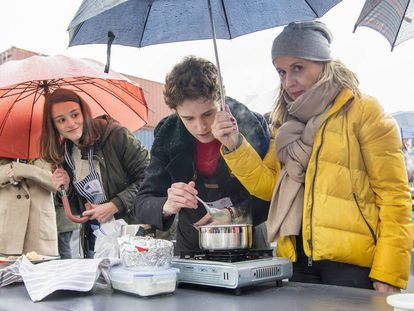 Una familiar de un concursante protege a este e la lluvia con un paraguas en la última prueba presencial para 'MasterChef' 6 en Getafe.