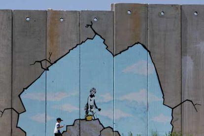 Un niño palestino pasa junto a una de las pinturas del muro de Gaza.