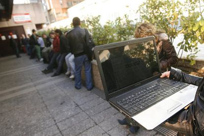 Una oficina de empleo en Madrid. Un joven busca ofertas laborales en su ordenador mientras espera la cola, una opción muy extendida.