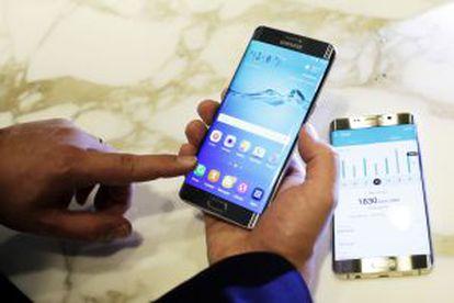 Un hombre sujeta el nuevo Samsung Galaxy S6 Edge Plus. Sobre la mesa, el Note 5