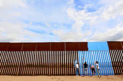 Voluntarios de Erasing the Border pintan la barrera entre EEUU y México para hacerla 'invisible'.
