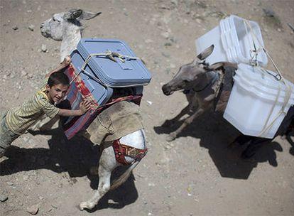 Un niño sujeta un burro cargado con urnas electorales en la provincia de Panshir.