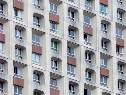 Un hombre mira por la ventana en un edificio de apartamentos de gran altura durante el segundo día de cierre ordenado por el gobierno francés para combatir el coronavirus el 18 de marzo de 2020 en París, Francia.