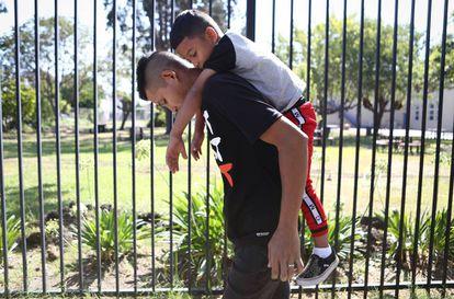 Un padre lleva a la espalda a su hijo de seis años en Oakland (California).