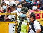 """People coming from Venezuela with protective face masks as a precautionary measure to avoid contracting the new coronavirus, COVID-19, show hold their documents on the border at Simon Bolivar International Bridge, in Cucuta, Colombia, on March 12, 2020. - Colombia declared on March 12, 2020 a """"Health Emergency"""" due to the new coronavirus pandemic, a figure that allows it to take exceptional measures such as prohibiting the disembarkation of cruise ships and the holding of public events with more than 500 attendees. (Photo by Schneyder MENDOZA / AFP)"""