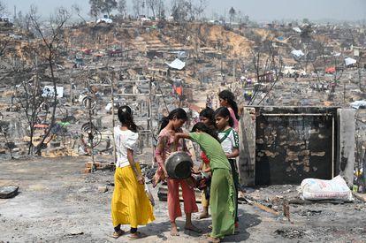 Vista general de la zona incendiada en el campamento de refugiados de Cox's Bazar. Un grupo de niñas rohinyá busca agua y comida para sobrevivir.