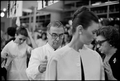 Cristóbal Balenciaga ajusta uno de sus modelos, en París en 1968.