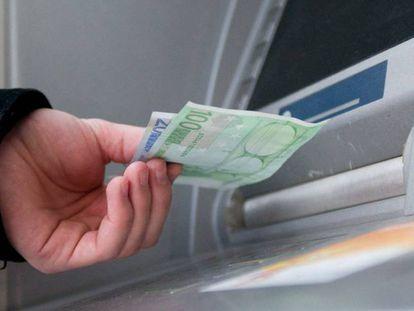 Un hombre saca euros de un cajero automático.