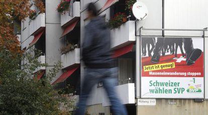 """Un transeúnte pasa ante un cartel del derechista SVP/UDC que llama a """"frenar la inmigración masiva"""""""