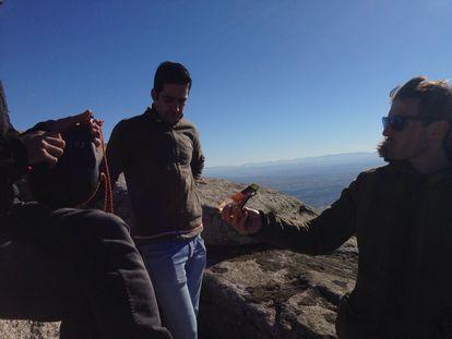 Miguel Corrales, a la derecha, ofrece unos frutos secos a sus amigos en el Piélago, en la sierra de San Vicente (Toledo).
