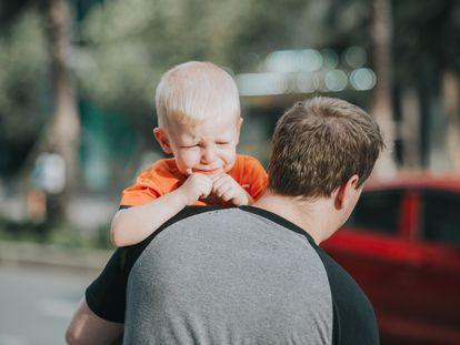 Un niño sufre una rabieta, mientras su padre trata de calmarle.