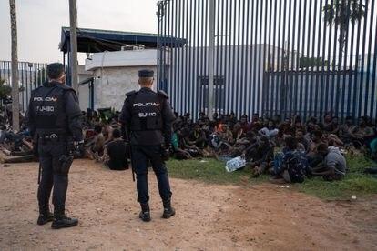 Agentes de la Policía Nacional junto al grupo de inmigrantes en las puertas del CETI de Melilla.