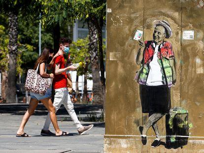 """GRAFCAT745. BARCELONA (ESPAÑA), 20/08/2020.- Unos jóvenes pasan ante un mural pintado por el artista urbano TV Boy titulado """"Viajando como un Rey"""" en la que se ve al Rey Emérito Juan Carlos I , este jueves en la Barceloneta. EFE/ Quique García"""