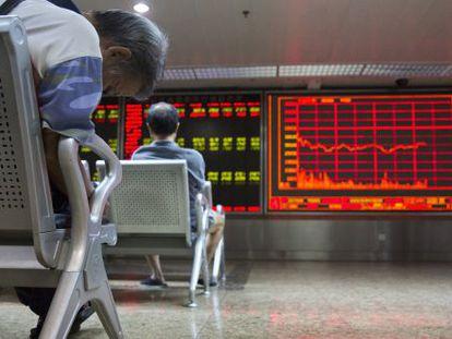 Dos inversores, este lunes, frente a un panel de cotizaciones en Pekín (China).