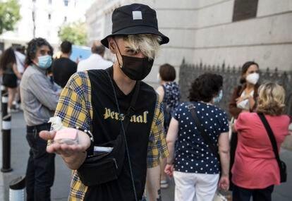 Unai Martínez sujeta las pesetas mientras espera la cola para cambiarlas en el Banco de España