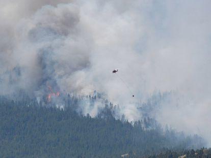 Un helicóptero intenta sofocar el incendio a las afueras de la ciudad de Lytton, arrasada por el fuego, el jueves.