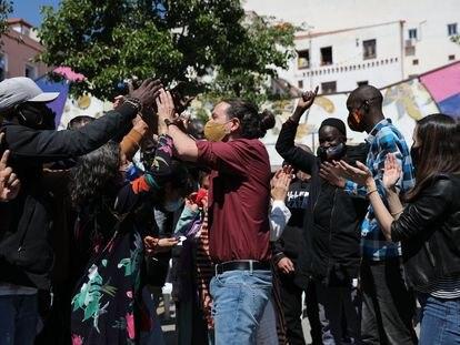 Pablo Iglesias, aclamado por un grupo de inmigrantes durante su acto electoral de este domingo en el barrio madrileño de Lavapiés.
