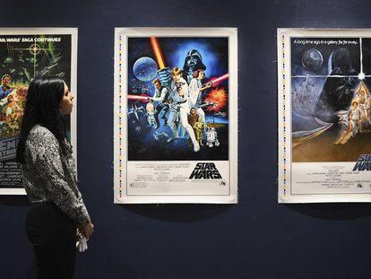 Una empleada de Sothebys observa unos carteles originales de las primeras películas de Star Wars que pondrá a subasta.