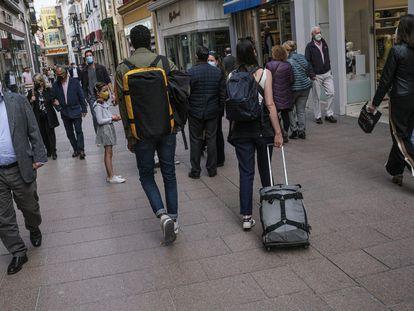 Unos turistas pasean por el centro de Sevilla.