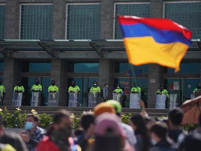 Manifestantes frente al edifico de la Fiscalía, resguardado por policías, en Bogotá.