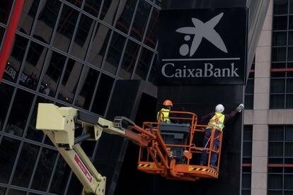 Dos operarios instalan el 27 de marzo el logo de CaixaBank, en el edificio de la sede de Bankia, en las torres Puerta de Europa de Madrid.