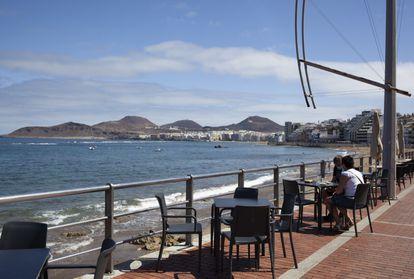 Dos personas sentadas en una terraza en la playa de Las Canteras, en Las Palmas de Gran Canaria.