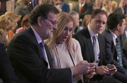 Rajoy muestra su móvil a Cifuentes, durante un acto del PP.