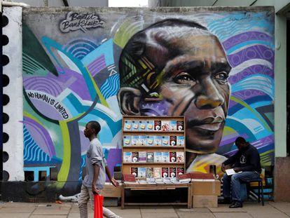Un hombre pasea junto a un graffiti con el poseedor del récord mundial de maratón de Kenia Eliud Kipchoge en una avenida en el centro de Nairobi, Kenia.