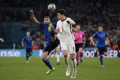 El italiano Domenico Berardi, a la izquierda, y el inglés Harry Maguire luchan por el balón durante la final de la Eurocopa 2020 en Wembley.