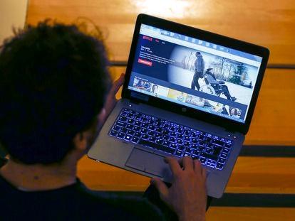 Una persona viendo una película en un ordenador portátil.