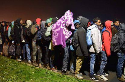 Inmigrantes hacen cola para subir esta mañana para subir a los autobuses que los trasladarán.