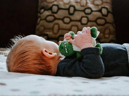 Un bebé está tumbado en su cama.