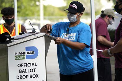 Una mujer sella uno de los buzones para depositar el voto por adelantado en el condado de Miami-Dade en las elecciones presidenciales del pasado noviembre.