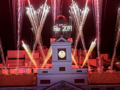 El reloj de la Puerta del Sol da las campanadas de fin de año, frente a la mirada de miles de personas.