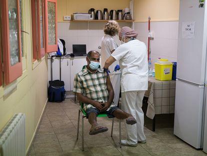 George, que habitualmente duerme en el parque de la Ciutadella, recibe una vacuna en la Fundació Arrels.
