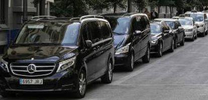 Una fila de vehículos de alquiler con conductor (VTC) y taxis en una calle de Madrid.