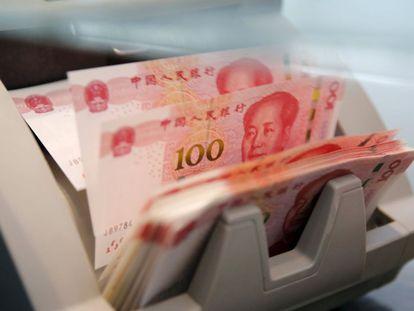 Una máquina cuenta billetes de 100 yuanes en un banco de Pekín.