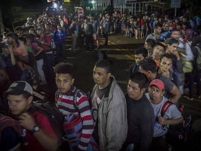 Centroamericanos de la caravana migrante esperan en fila para acceder al puesto fronterizo de El Ceibo, Tabasco (México).