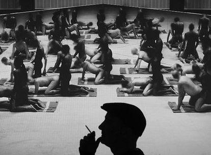 El artista Santiago Sierra, fotografiado en penumbra, con su obra <i>Los penetrados</i> de fondo.