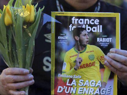 Un seguidor del Nantes sujeta este martes un ramo y una revista de 'France Football' con la imagen de Emiliano Sala. En vídeo, el audio de WhatsApp que Sala envió a sus amigos antes de que se perdiera su rastro.