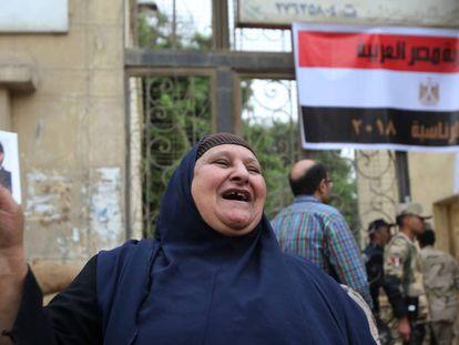Una egipcie sostiene una foto de Abdelfatá al Sisi en la entrada de un colegio electoral en El Cairo, este miércoles.
