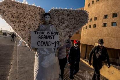 Un grupo religioso caracterizado como ángeles rezan a las afueras del hospital regional de Juárez.