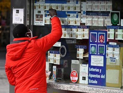 Un joven señala un billete de lotería en un establecimiento de Madrid.