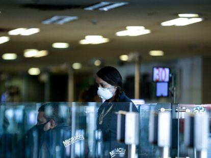 Una trabajadora del aeropuerto de Bogotá utiliza un cubrebocas.