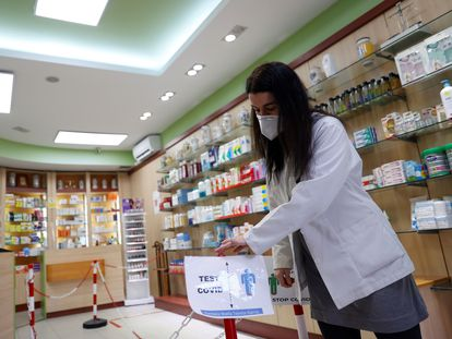 Una empleada de una farmacia madrileña coloca un cartel en su interior el pasado 1 de febrero.