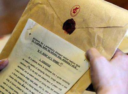 Artículo científico sobre fisión nuclear, con el sobre y el sello con la C y la huella dactilar de Chadwick.