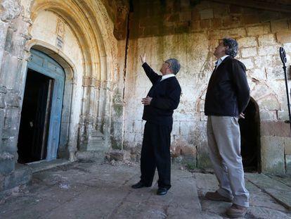 El responsable de Patrimonio del Obispado de Palencia, José Luis Calvo, señala la grieta en la que se ha encontrado la pieza tallada en piedra. A la derecha, el descubridor del hallazgo, José María Menéndez Jambrina.