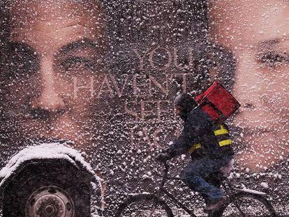 Un repartidor pasa frente un camión en Nueva York.