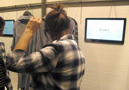 Una mujer se prueba una prenda en un vestidor dotado con tableta, en Zara SanSebastián.